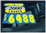 A used car window displaying a dealership sale sign