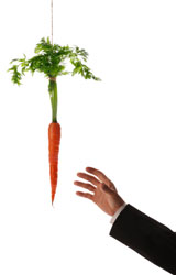A carrot dangling on a string in front of a man's hand