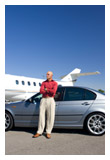 A man standing in front of a luxury car and a private plane