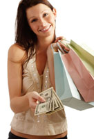 A pretty woman with shopping bags and a hand full of cash