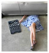 Woman in a dress repairing a car