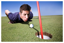 Golfer blowing his ball into the hole