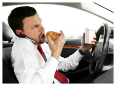 Man eating, drinking coffee, talking on a cell phone and driving