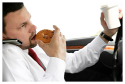 A man eating, drinking coffee, taking on the phone and driving