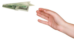 A hand throwing a paper airplane made from a dollar